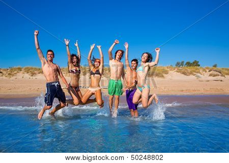 Happy excited teen boys and girls group jumping at the beach splashing water