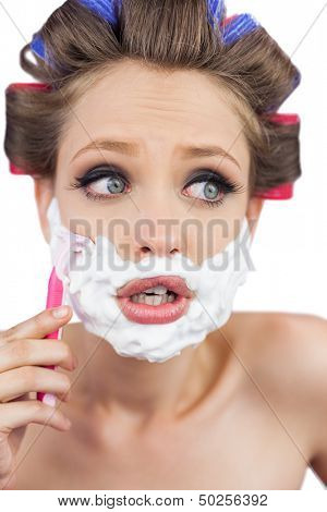 Shocked young model in hair curlers posing with razor on white background