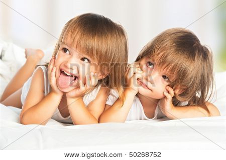 Happy Little Girls Twins Sister In Bed Under The Blanket Having Fun