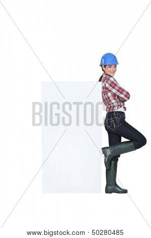 Tradeswoman leaning against a blank sign