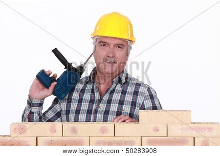 Tradesman holding a power tool and standing behind a brick wall