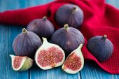 Group of figs in a bowl and on rustic blue wooden table poster
