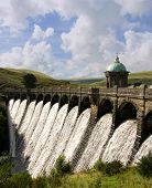 Water overflowing a dam Craig Goch reservoir Elan Valley Wales. poster