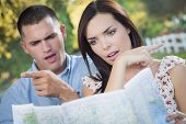 Lost and Confused Mixed Race Couple Looking Over A Map Outside Together. poster