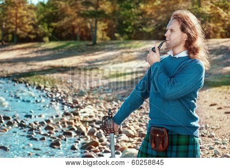 Handsome scottish man with sword and pipe outdoor poster