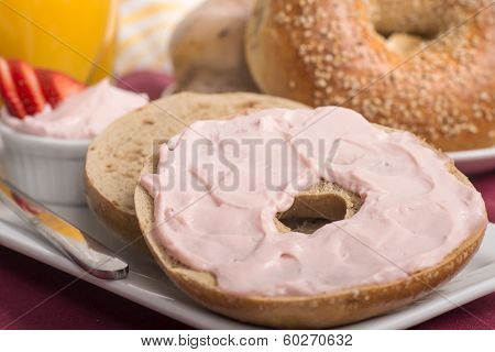 Freshly made sesame bagel with strawberry cream cheese, orange juice and ripe sliced strawberries