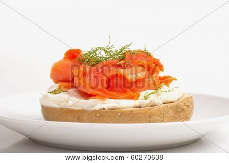 Freshly made bagel with cream cheese, salmon and dill on a white background
