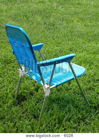 Child's lawn chair alone in the grass. poster