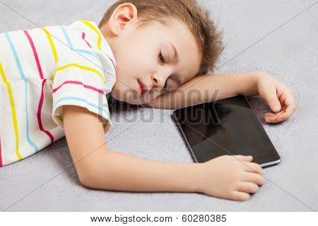 Little tired sleeping child boy hand holding digital tablet computer