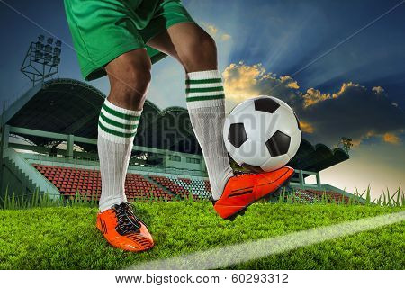 Foot Ball Player Holding Foot Ball On Leg Ankle On Soccer Sport Field Agianst Stadium And Dusky Sky