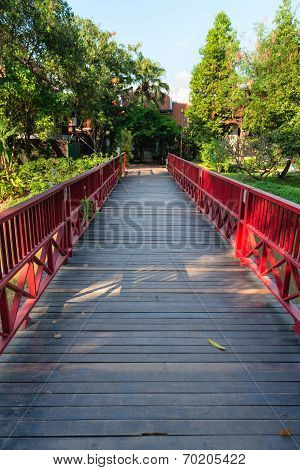 Wooden bridge with red fence in green park