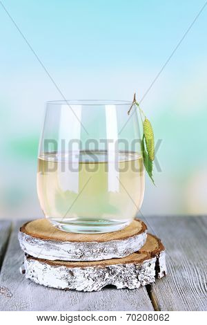 Glass of fresh birch sap on a wooden table on nature background