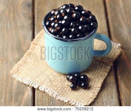 Ripe blackcurrants in mug on sackcloth napkin, on wooden background.