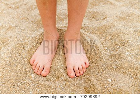 Bare feet of a young child in the sand poster