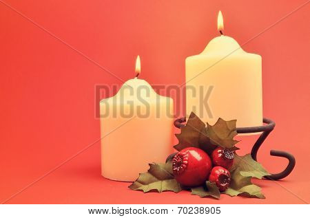 A Pair Of Two Creamy White Lit Candles With Greem And Red Holly Decoration Against A Red Orange Back