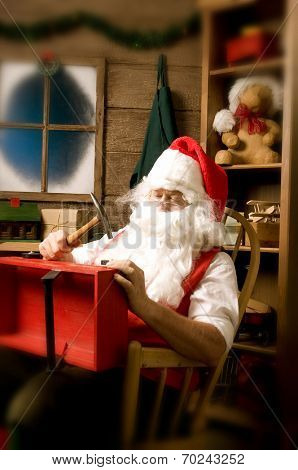 Santa Claus sitting in Rocking Chair in Workshop With Red wooden Wagon on his Lap. Vertical Composition with an intentional vignette