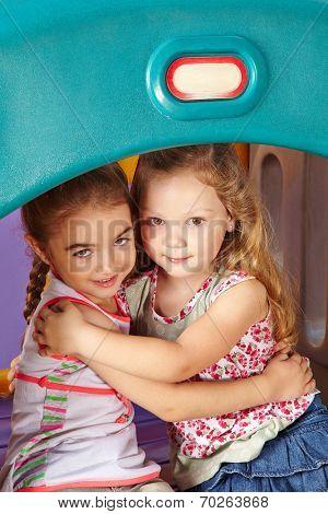 Two befriended girls embracing in a kindergarten