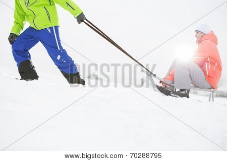 Low section of man giving sled ride to woman in snow poster