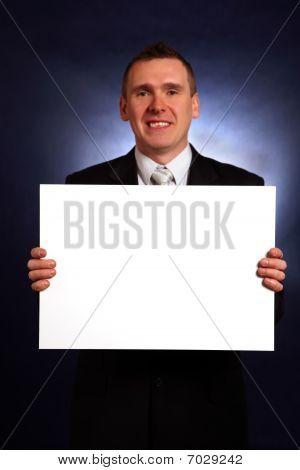Smiling Businessman Holding A Big Blank Card