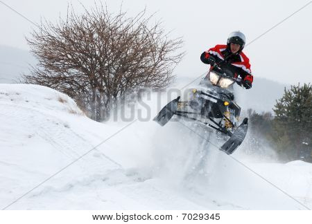 Young man on the snowmobile jumping high