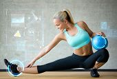 fitness, sport, training, future technology and lifestyle concept - smiling woman with exercise ball in gym over graph projection poster