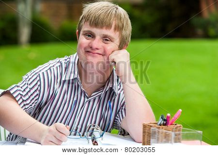 Boy With Down Syndrome At Desk Holding Glasses.