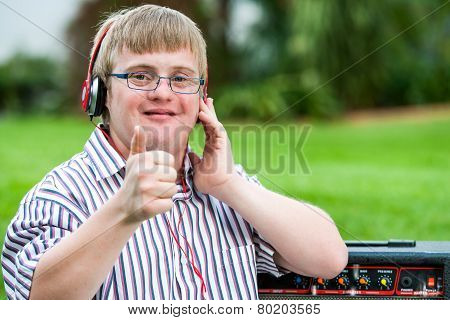 Down Syndrome Boy With Headset Doing Thumbs Up.