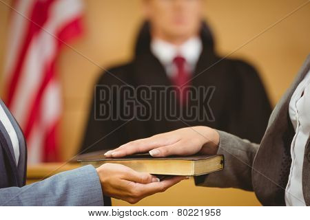 Witness swearing on the bible telling the truth in the court room poster