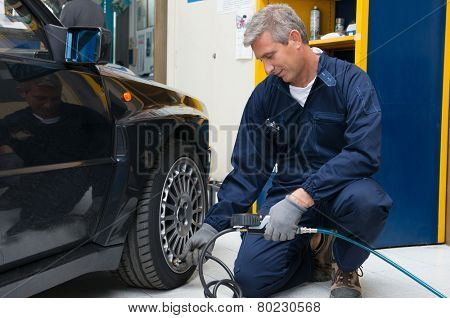 Portrait Of Happy Mature Mechanic At Repair Service Station Checking Tyre Pressure