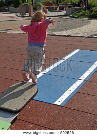 Young girl jumps from spring board
