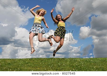 Two Girls Jumping In Grass Field
