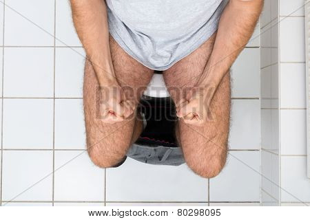 Man Clenching His Fist Sitting On Toilet Bowl