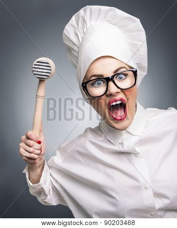 Mad Woman Cook With A Hammer Punching You, Isolated On Gray. Humorous Concept