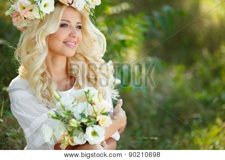 Portrait of a beautiful bride on floral swing in the Park.