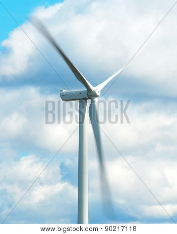 Moving wind turbine over the blue sky.