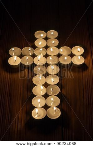 Lit tea lights in the shape of a cross on old wooden background