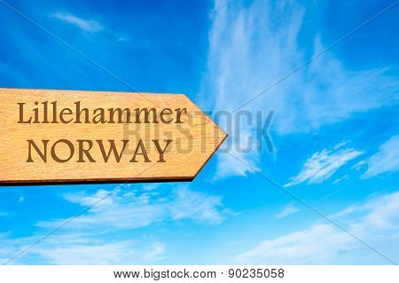 Wooden arrow sign pointing destination LILLEHAMMER NORWAY against clear blue sky with copy space available. Travel destination conceptual image poster