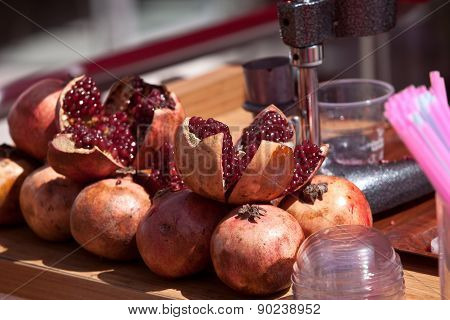 Split pomegranates ready to be juiced on Turkish street vendor table poster