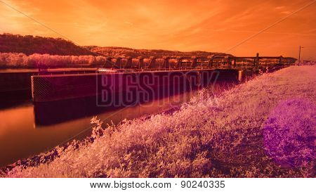 Infrared Lock and Dam on a River. Sun Flair. Orange Colorization.