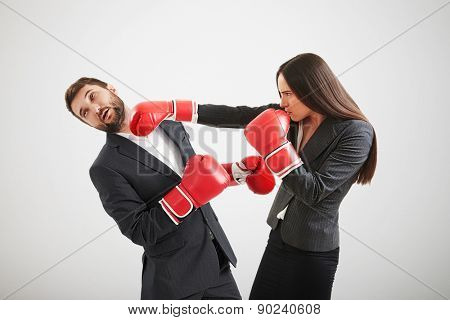 angry businesswoman in red boxing gloves punching businessman over light grey background poster
