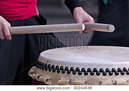 Group of japanese musicians are playing on traditional japanese percussion instrument Taiko or Wadaiko drums. The drumsticks are in the hands. poster
