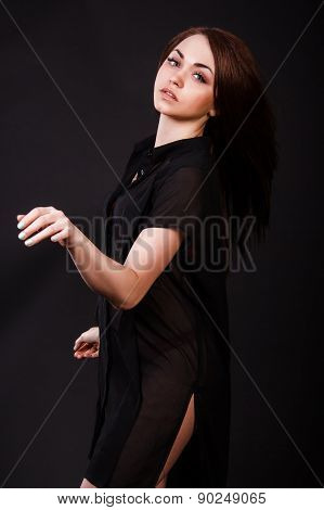Amazing young woman in a red underwear and a black peignoir with a flying hair over black background poster