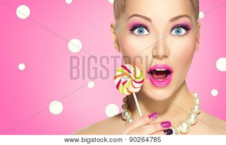 Beauty fashion model girl Eating colourful lollipop. Surprised Young funny woman with pink nail art and makeup over pink polka dots background
