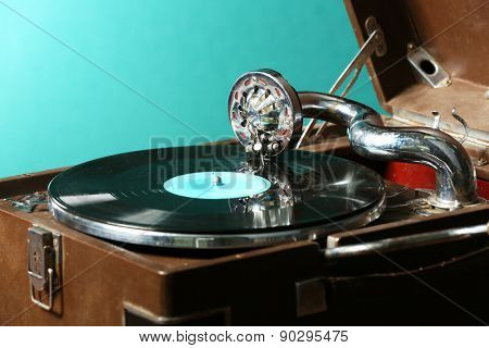 Gramophone with vinyl record on table on green background