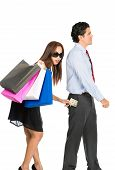 A shopaholic greedy Asian wife with sunglasses department store bags steals money unnoticed from the pants pocket of her husband as he walks away poster