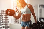Strong woman bodybuilder with white hair and tanned body pumps up the muscles lifting dumbbells in the gym. Horizontal frame with space for text poster