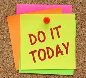 The phrase Do It Today on a yellow sticky note pinned to a cork notice board as a reminder poster