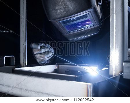 Skilled worker welding metal together in a welding factory