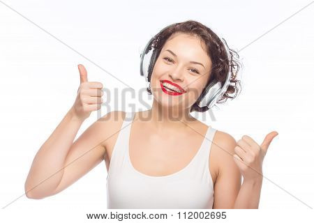 Woman in headphones showing thumbs up.