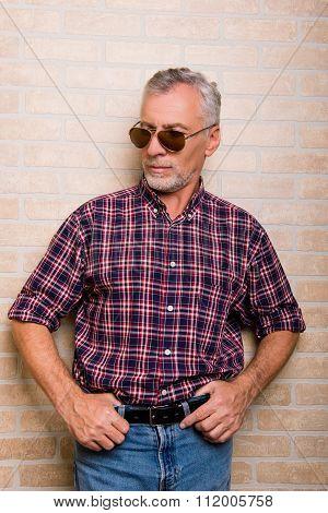 Portrait Of Senior Aged Man In Glasses On Bricks Background